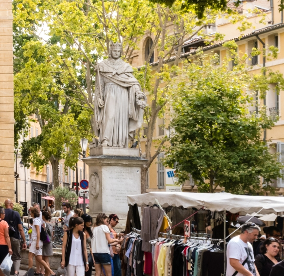 A stone statue of King Rene (who died in Aix-en-Provence in 1480) holding a scepter in this right hand and a bunch of Muscat grapes on the left sits above a fountain at the eastern end of Cours Mirabeau, Aix-en-Provence, France