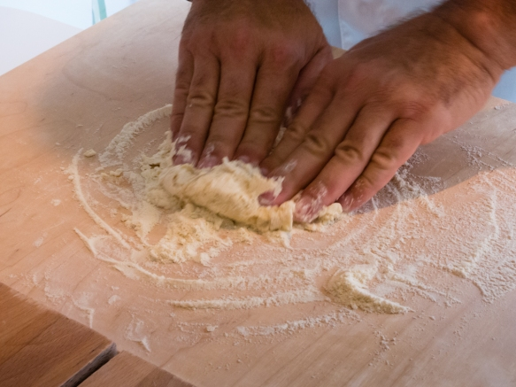 After the water is blended into the flour, we were shown how to begin the hand kneading on the wooden board