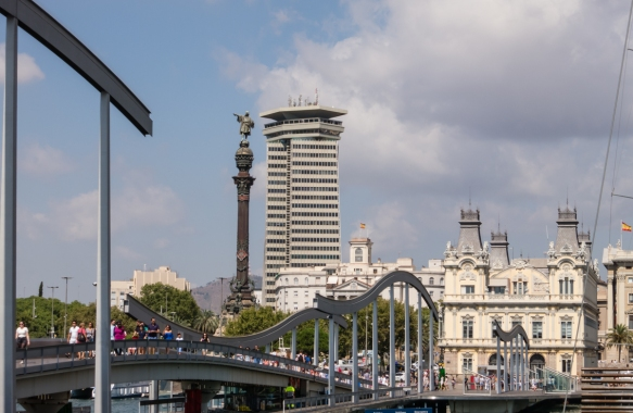 Close up of the Monument Colon (Christopher Columbus column) (on the left) and the pedestrian (bridge) Rambla de Mar (to the Barcelona Aquarium), Port Vell, Barcelona, Spain