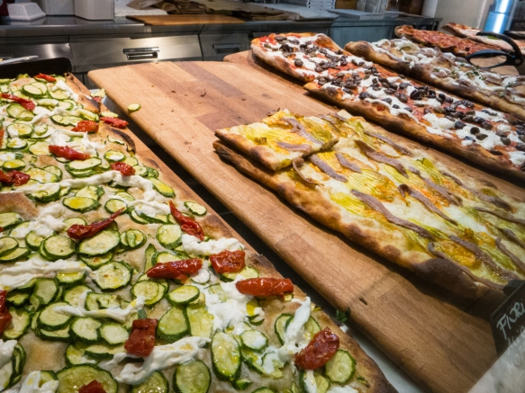 "One of the many restuarants and ""cafes"" in Ealaly, Roma, Italy, featured fresh, hand-made flatbreads with very interesting toppings (e.g., zucchini and cheese with sun-dried tomatoes, on the left)"