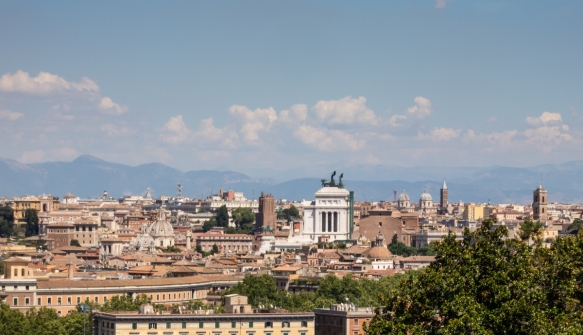 "Our first view of Roma, Italy, from the west, driving into the city center with the ""Wedding Cake"" (Monumento Nazionale a Vittorio Emanuele II) in the center (with the chariot on top); note church domes dominate the skyline, taller than any buildings"