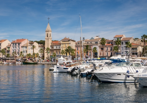 Sailing into the harbor of Sanary-sur-Mer, France, the Gothic Revival church, Eglise Saint Nazaire's bell tower dominates the skyline