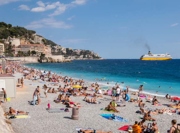 The eastern end of Plage Promenade des Anglais (English Promenade Beach) under Parc de la Colline du Chateau (Castle Hill Park) with a car-passenger ferry heading for Sardinia or Corsica; Nice, France