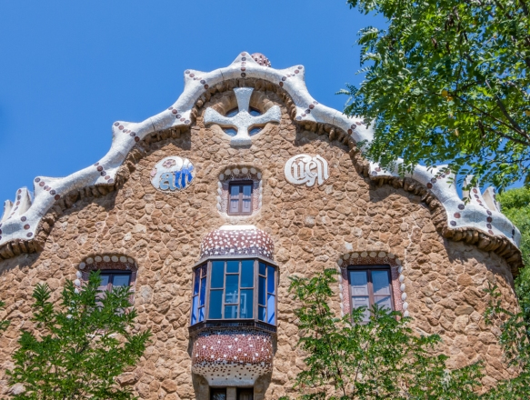 "The façade of one of the Gaudí-designed buildings along the entry street to Parc Guell (note the park's name in the upper two ""circles""), Barcelona, Spain"