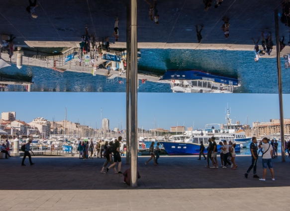The ships in Vieux Port (Old Port) reflected in English architect Norman Foster's polished steel Vieux Port Pavillion at the east end of the port on Quai des Belges, Marseille, France