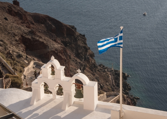 a-greek-flag-and-belfry-photographed-just-before-sunset-oia-santorini-island-greece