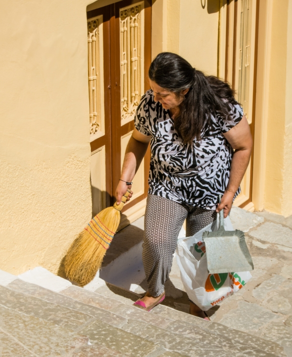 a-local-homeowner-cleaning-the-public-path-steps-in-front-of-her-home-in-old-town-symi-greece