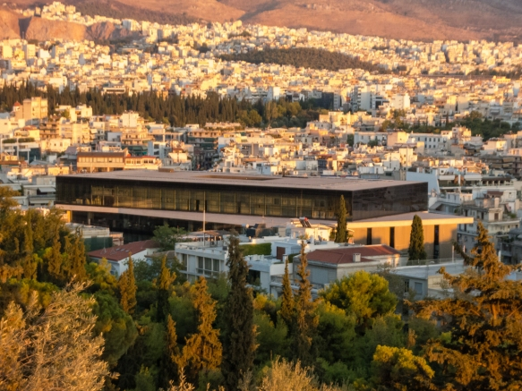 a-sunset-view-of-the-new-acropolis-museum-athens-greece-taken-from-just-above-the-odeon-of-herodes-atticus-while-walking-up-the-steps-to-the-entrance-to-the-acropolis
