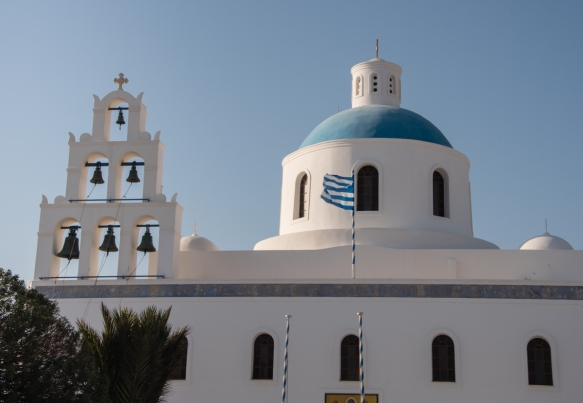 a-white-painted-church-with-a-large-six-bells-belfry-and-blue-cupola-oia-santorini-island-greece