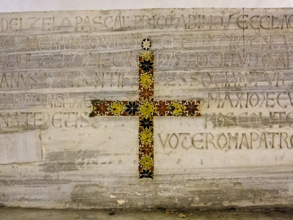 In the underground house below Basilica Santa Cecilia are many ancient Roman artifacts – this tombstone, inscribed in Latin on the obvers side, was recycled a few hundred years later after Christianity took root in Roma, Italy