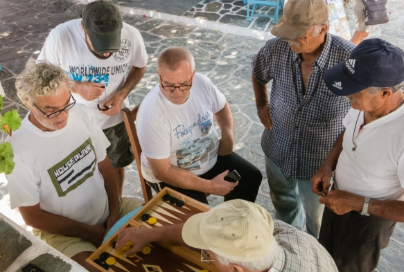 local-men-playing-backgammon-before-lunch-in-a-town-square-in-chora-folegandros-island-cyclades-greece