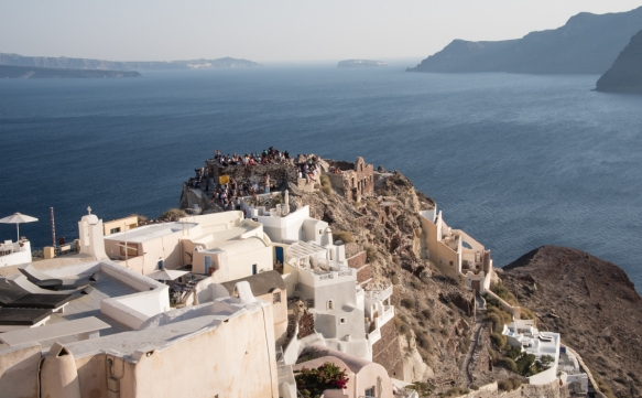many-people-head-to-the-tip-of-oia-santorini-island-greece-well-in-advance-of-sunset-in-order-to-have-their-spot-to-celebrate-the-colorful-santorini-sunset