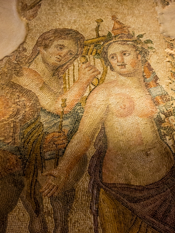 mosaics-from-the-house-of-aion-3rd-5th-c-a-d-portion-of-the-lower-left-panel-of-the-central-panel-in-the-main-room-showing-a-half-naked-maenad-leading-the-triumphal-procession-of-the