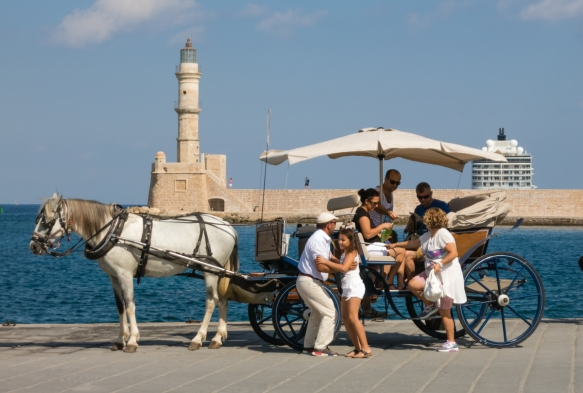 one-of-the-citys-many-horse-drawn-carriages-in-front-of-the-lighthouse-of-chania-circa-1595-1601-that-is-one-of-the-oldest-lighthouses-in-greece-and-the-mediterranean-but-also-in-the-world