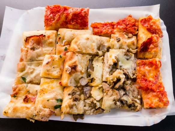"""Pizza is served in wedges that are then hand cut into bite size """"slices"""" at Pizzeria Rustica and piled onto a tray for eating al fresco under the trees at Plazza Liberta, Gaeta, Italy; our favorite was the white (no tomato sauce) prosciutto and cheese"""