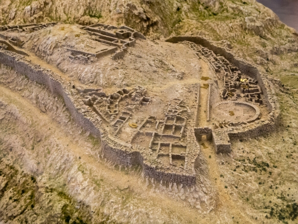 scale-model-of-the-mycenae-acropolis-in-the-sites-museum-showing-the-famous-lion-gate-1-the-monumental-entrance-to-the-fortified-citadel-the-palace-top-center-and-numerous-houses