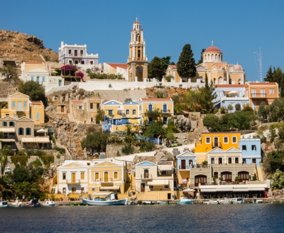 the-brightly-painted-shops-houses-and-churches-are-terraced-straight-up-the-hills-surrounding-the-harbors-of-symi-greece
