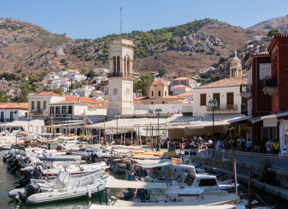 the-harbor-quayside-is-lined-with-shops-and-restaurants-with-outdoor-seating-hydra-greece