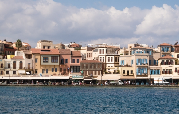 the-old-towns-pastel-colored-houses-form-a-tightly-hugged-semicircle-around-the-harbor-split-by-narrow-alleyways-chania-crete-greece