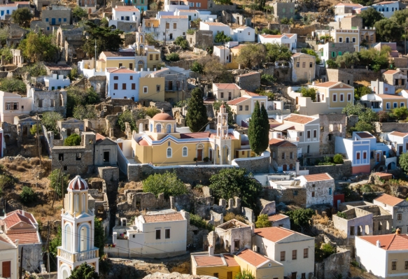 the-upper-portion-of-the-old-town-of-symi-greece-that-is-not-visible-from-the-harbor-behind-the-church-at-the-top-of-the-hill