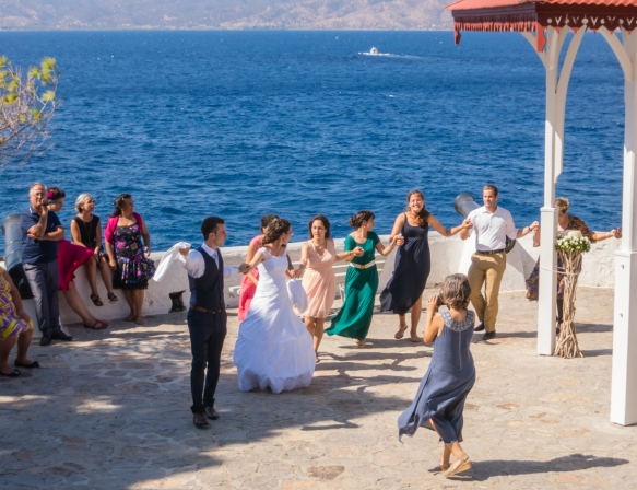 we-enjoyed-the-music-and-festivities-as-we-were-hiking-when-we-came-across-a-groom-leading-his-bride-in-a-celebratory-dance-at-a-wedding-on-a-seaside-terrace-hydra-greece