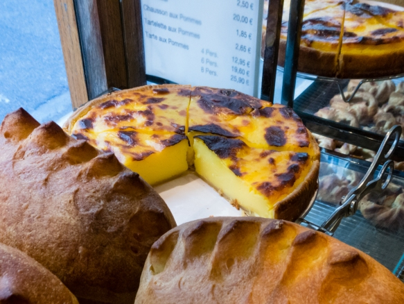 beautiful-brown-loaves-of-bread-at-poila%cc%82ne-bakery-along-with-one-of-their-popular-tarts-with-the-individual-tartelette-aux-pommes-apple-tarts-on-the-shelf-below-paris-by-mouth-taste-of-sa