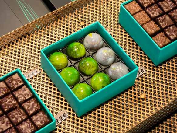 the-jewel-like-beautiful-green-chocolates-in-the-center-box-are-filled-with-a-chocolate-ganache-delicious-at-mof-patrick-rogers-chocolate-shop-on-saint-sulpice-in-saint-gremain