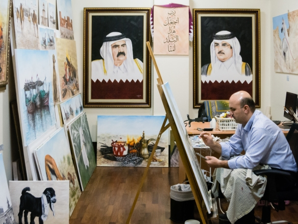 a-local-artist-with-paintings-of-local-scenes-in-his-gallery-with-portraits-of-the-former-emir-king-of-qatar-sheikh-hamad-bin-khalifa-bin-hamad-bin-abdullah-bin-jassim-bin-mohamm