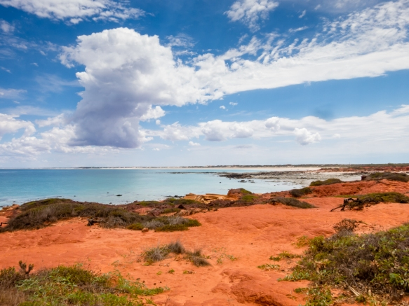 the-clear-waters-of-the-indian-ocean-bathe-the-white-sands-of-cable-beach-a-pristine-14-mile-22-km-stretch-of-beach-perfection-visible-beyond-the-red-sandstone-rock-formations-at-gantheaume-point