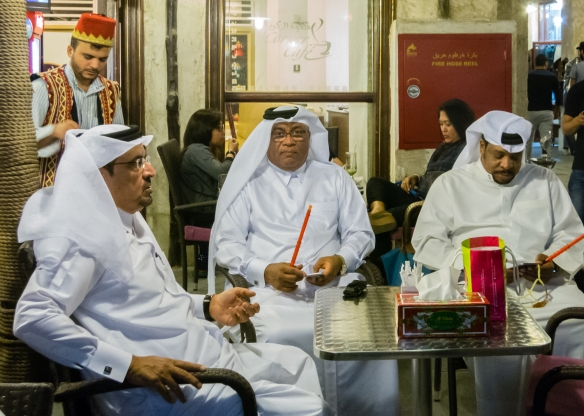 three-local-qatari-men-enjoying-hookahs-while-checking-their-cellphones-and-dining-outdoors-at-souq-waqif-doha-qatar