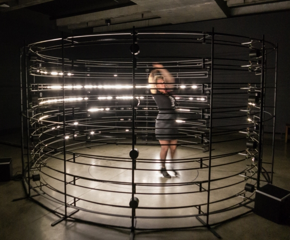 a-kinetic-sculpture-that-the-visitor-enters-and-then-moves-his-her-arms-and-dances-to-conduct-music-and-a-light-show-on-the-perimeter-of-the-exhibit-a-docent-is-demonstrating-moveme