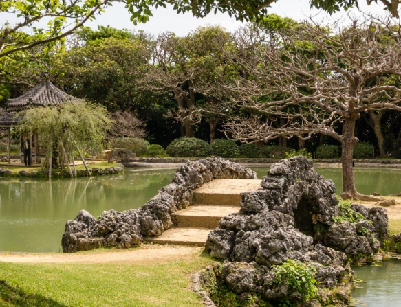 A classical Japanese arch footbridge on the pond at Shikinaen Royal Garden, Naha, Okinawa, Japan; the circular landscape garden design at Shikinaen became very popular among Japanese feu