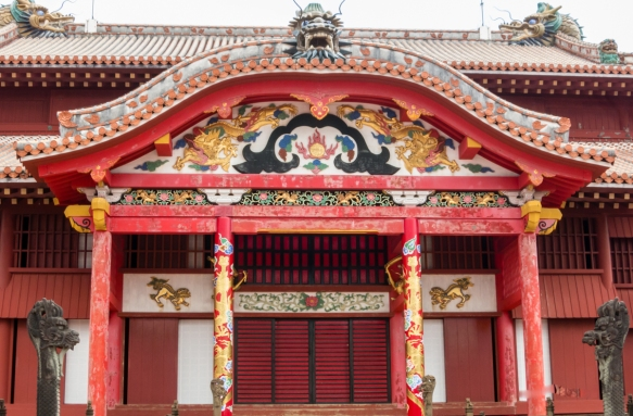Details of the front entrance to the Seiden at Ryukyu Castle, Naha, Okinawa, Japan; the Seiden is decorated with a variety of carved art (including a golden dragon), two great dragon pil