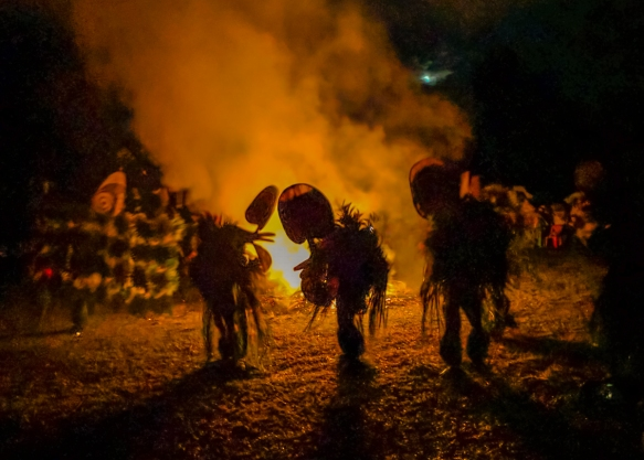 "Four masked dancers and a couple of men walking around the fire with a highly decorated ""banner"", Baining fire dance, Rabaul, Papua New Guinea; there was a break in the rain and the"