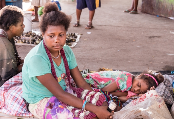 In the fish and seafood section of the Central Market, Honiara, Guadalcanal, Solomon Islands, a vendor_s daughter laid down for a rest