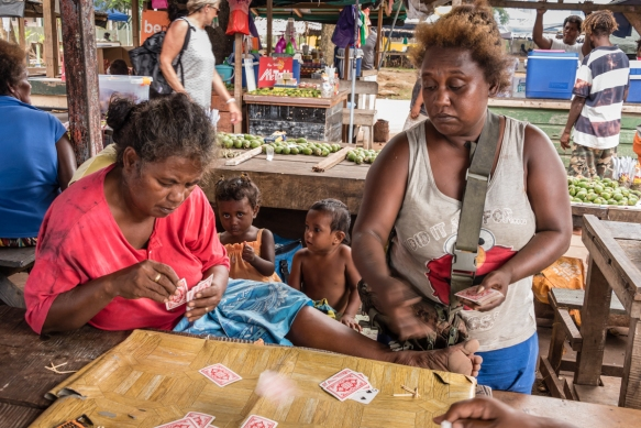 Separate groups of men and ladies were playing cards on the side of the Central Market, Gizo, Ghizo Island, Solomon Islands