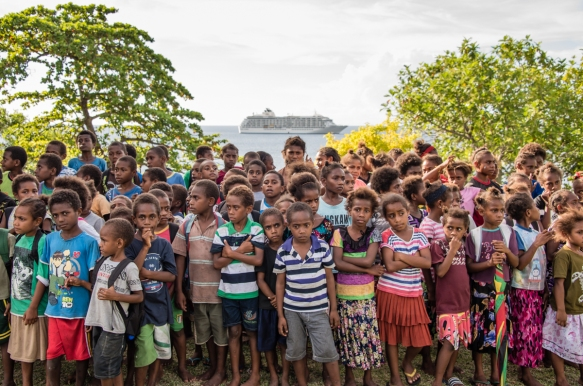 the-childrens-school-choir-gathered-in-their-school-yard-at-ranon-village-on-ambrym-island-vanuatu-with-our-ship-visible-in-the-background