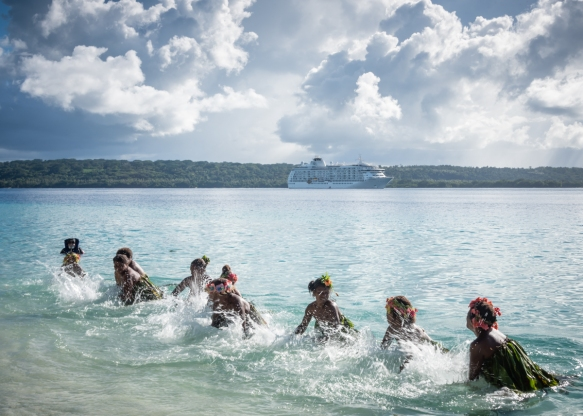 "The ""Water Women"" performing in the surf with our ship visible at anchor in the channel and Espiritu Santo Island in the background, Mavea Island, Vanuatu"