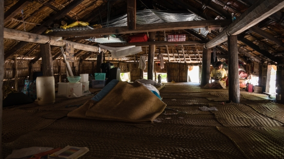 The inside of the house has a tamped earthen floor covered by many mats woven from local plant materials, Tikopia, Solomon Islands; note that one_s entrance to the house is by crawling