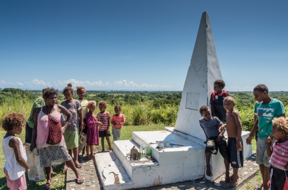 The small memorial on Bloody Ridge, Guadalcanal Island, Solomon Islands, with local islanders mingling with the visitors, offering war memorabilia for sale