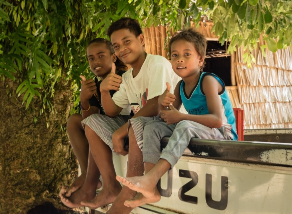 These kids wished us a warm farewell, sitting on the back of one of our transport 4-wheel drive trucks with seats for us in the cargo area, Titiana Village, Ghizo Island, Solomon Islands