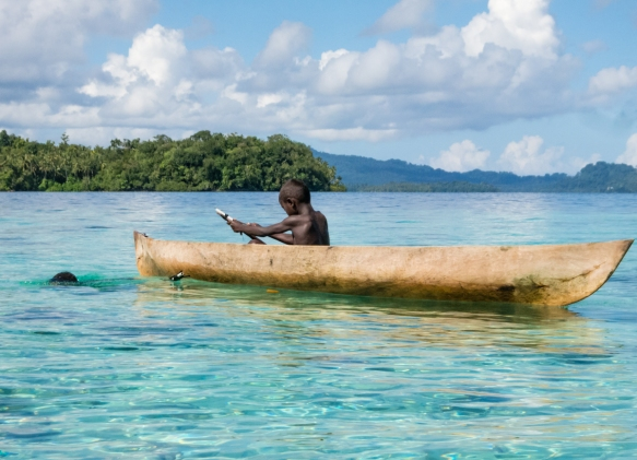 Two young islanders from Sabulo Island diving for fish, Marovo Lagoon, Solomon Islands