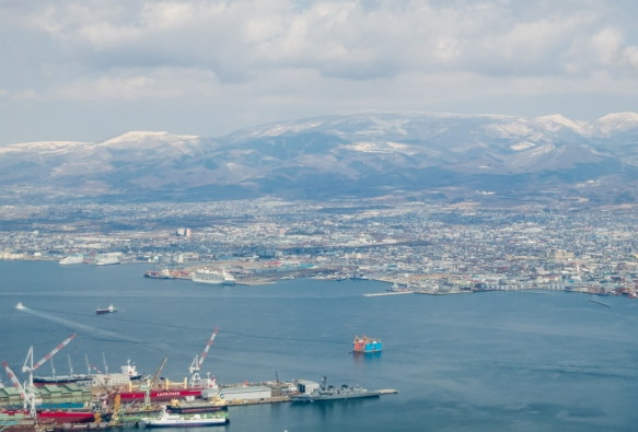 A view of the west bay from Mt. Hakadote with our ship docked (mid-left, above the large, red, right-hand crane in the foreground), Hakodate, Hokkaido Island, Japan; note the snow on the