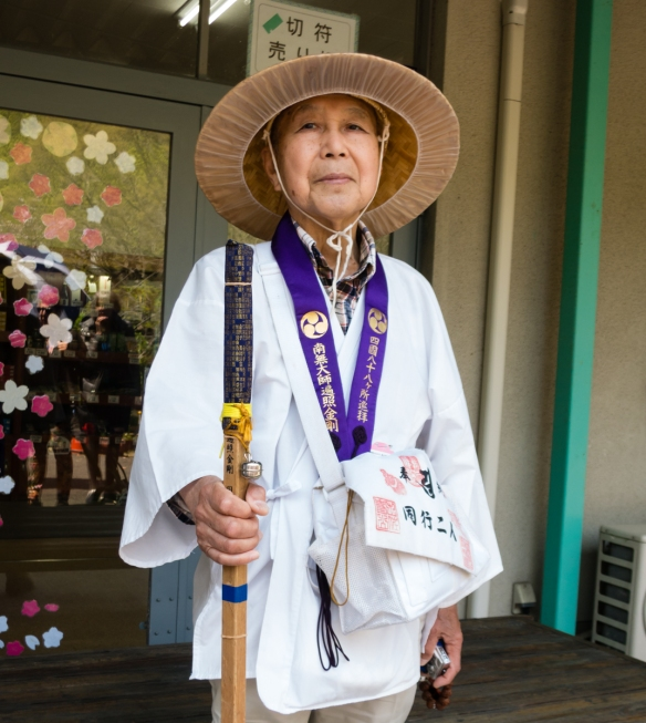 One of several modern day pilgrims that we met on our walk, known as o-henro-san (お遍路さん), in a white jacket emblazoned with the characters Dōgyō Ninin (同行二人), meani
