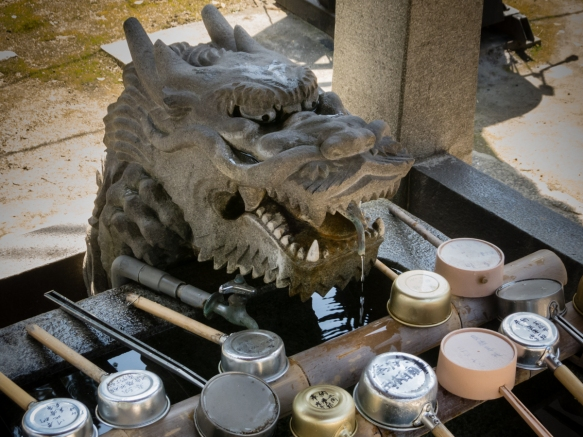 Pilgrims and other praying visitors ceremonially wash their hands twice and rinse their mouths with water from the dragon-guarded water basin before prayers at Yashimaji Temple #84 on th