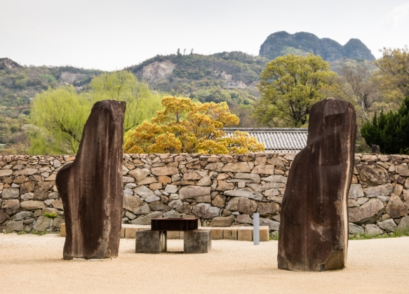 Sculptures outside the wall of the outdoor sculpture garden at the Isamu Noguchi Garden Museum, Takamatsu, Shikoku Island, Japan, set against the surrounding mountains