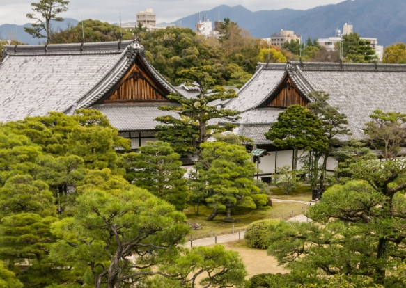 Several of the buildings of Nijo-jo Castle, Kyoto, Japan, set in the gardens, with modern-day Kyoto in the background