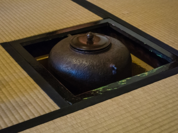 The hot water for the tea is heated in a kama (kettle) that is placed on (and heated by) the furo (charcoal brazier) that is built into the floor of the tea-room, Japanese Tea House, Kyo
