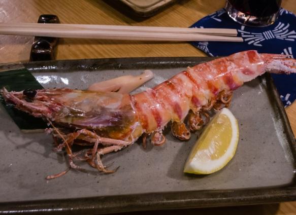 The iridescent kuruma-ebi (tiger prawn) was skewered while it was still alive, then grilled at Inakaya (Roppongi East), Tokyo, Japan
