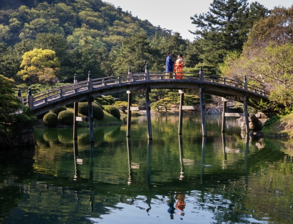 The wedding couple posed upon the most photographed bridge in Ritsurin Garden, Takamatsu, Kagawa, Japan, on Nanko Pond – this bridge is one of the iconic images of Japanese gardens